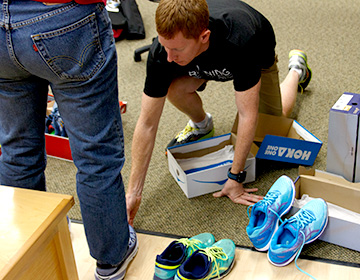 male store salesperson checking the fit of running shoes on a customer's right foot